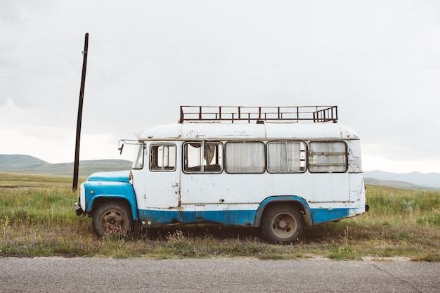 Primer plano de un viejo minibús en un paisaje verde bajo un cielo nublado