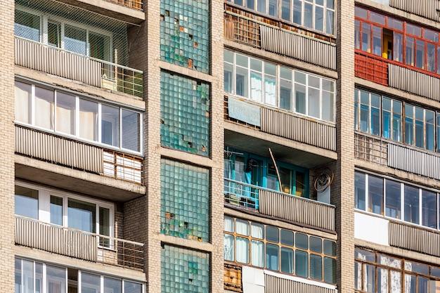 Primer plano de viejos balcones acristalados de una casa de paneles de varios pisos en un área para dormir. fachada de una casa antigua