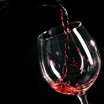 Primer plano de vino vertiendo en vidrio