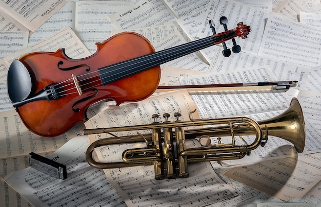 Primer plano de un violín y una trompeta en hojas de notas bajo las luces