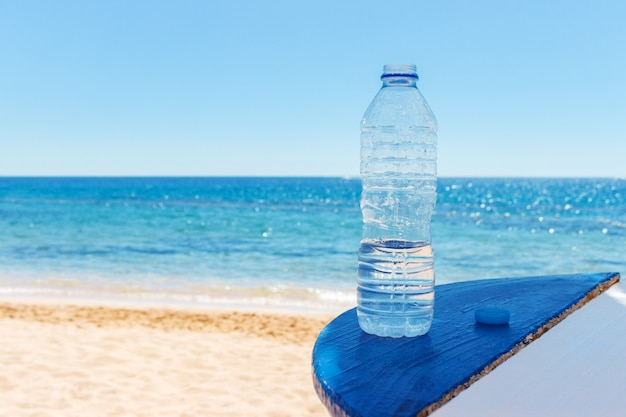 Primer plano de la vista al mar y botella de plástico con agua en mesa