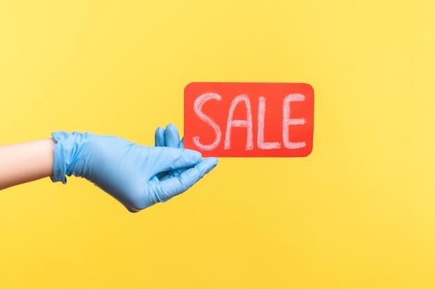 Primer plano de la vista lateral del perfil de la mano humana en guantes quirúrgicos azules que sostienen y que muestran la etiqueta roja de la venta.