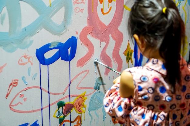 Primer plano y vista posterior de una niña asiática dibujando y decorando las paredes de su nuevo aula de arte