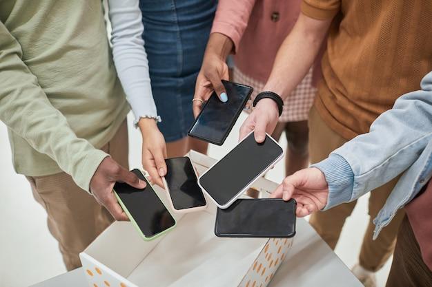 Primer plano de la vista superior de un grupo diverso de adolescentes poniendo teléfonos inteligentes en la caja en un aula sin gadgets en la escuela, espacio de copia