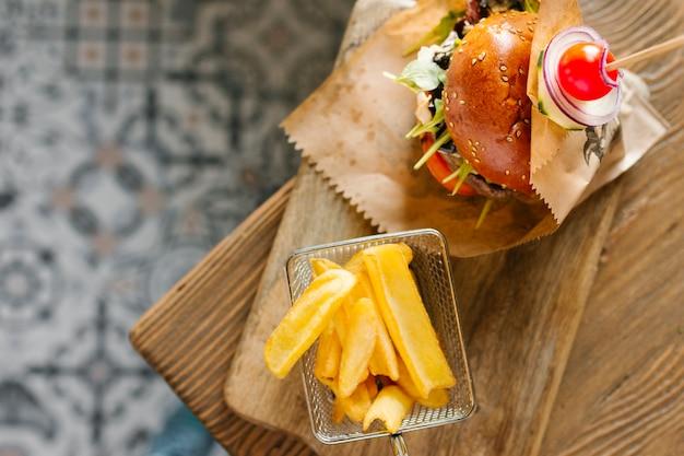 Primer plano de la vista superior de hamburguesa y papas fritas en tablero de madera