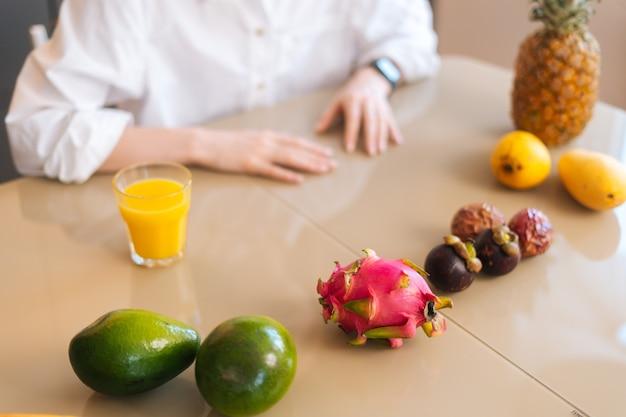 Primer plano vista superior de irreconocible joven sentado en la mesa de madera con frutas tropicales exóticas en