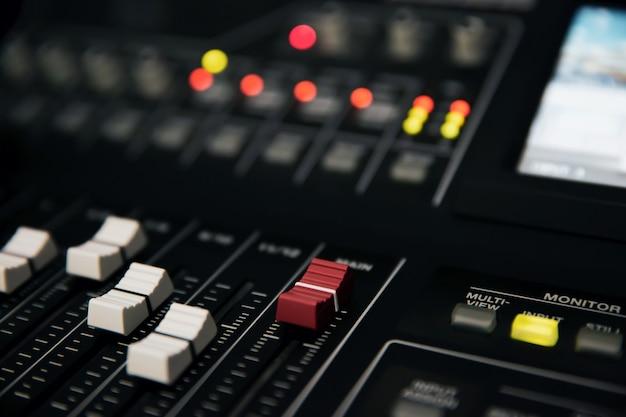 Primer plano del volumen de ajuste en el mezclador de sonido en el lugar de trabajo del estudio.