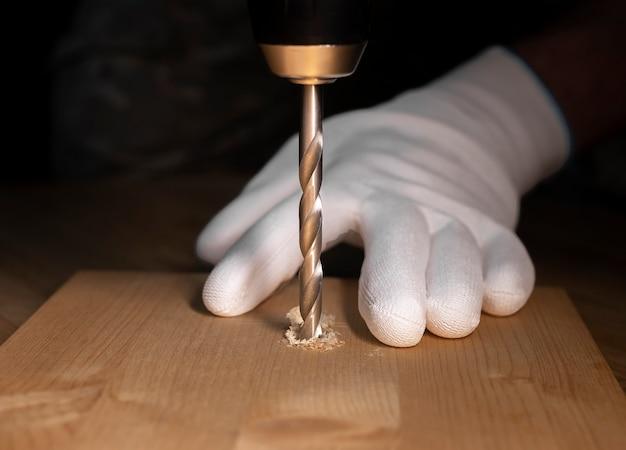 Primer del proceso de trabajo de perforación. taladro de acero moderno que hace un agujero en la madera y las manos en los guantes del constructor.
