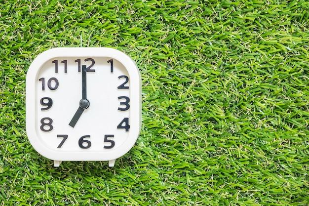 El primer reloj blanco para decorar a las 7 en punto en el suelo de césped artificial verde