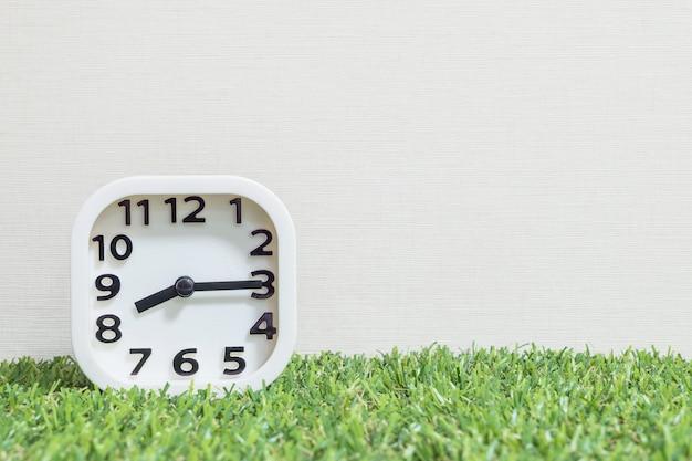 El primer reloj blanco para decorar muestra las ocho y cuarto o las 8:15 de la mañana en un piso de césped artificial verde