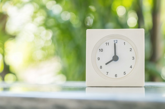 Primer reloj blanco en la mesa de mármol borrosa en el fondo del jardín