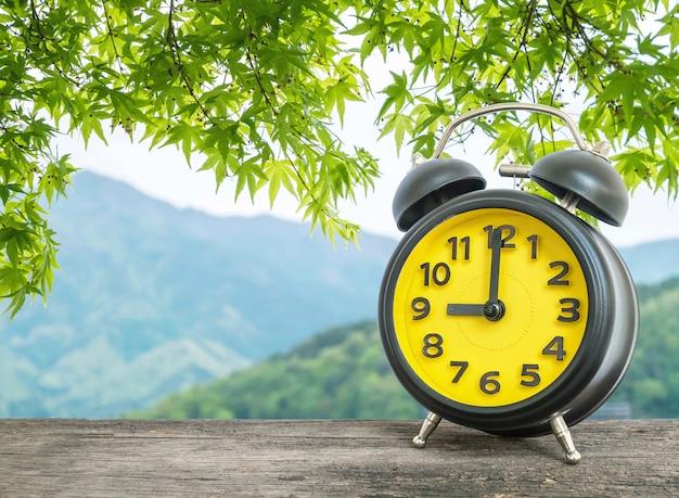 Primer reloj despertador a las 9 en punto en la mesa