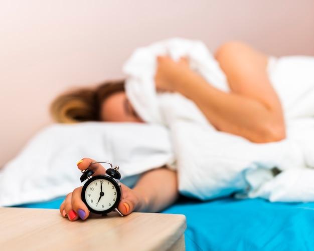 Primer reloj despertador sostenido por una mujer soñolienta