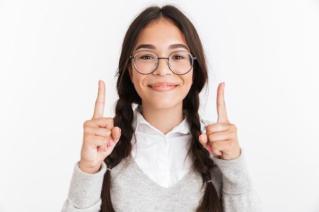 Primer retrato de una adolescente alegre con anteojos sonriendo y apuntando con el dedo hacia arriba en copyspace aislado sobre la pared blanca
