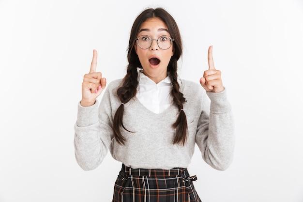 Primer retrato de una adolescente encantada con anteojos preguntándose y señalando con el dedo hacia arriba en el copyspace aislado sobre la pared blanca