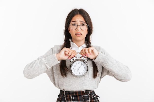 Primer retrato de una adolescente perturbada con anteojos frunciendo el ceño mientras sostiene el despertador en las manos aisladas sobre la pared blanca