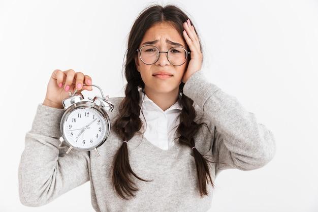 Primer retrato de una adolescente preocupada con anteojos frunciendo el ceño mientras sostiene el despertador en las manos aisladas sobre la pared blanca