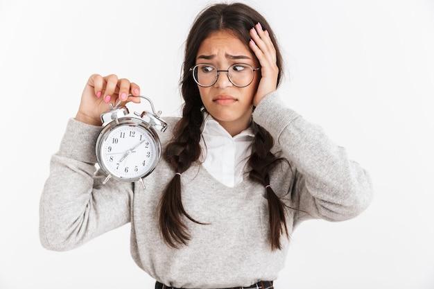 Primer retrato de una adolescente tensa que usa anteojos frunciendo el ceño mientras sostiene el despertador en las manos aisladas sobre la pared blanca
