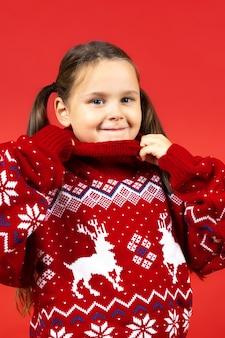 Primer retrato de niña linda en suéter rojo de navidad con renos sosteniendo el collar con las manos isola ...