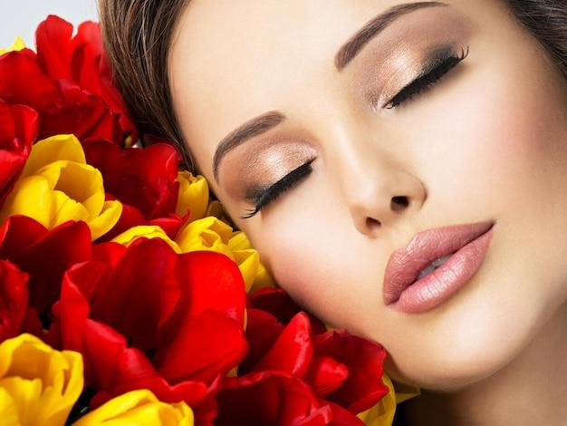 Primer rostro de belleza de la mujer joven con flores. modelo atractivo con tulipanes rojos y amarillos