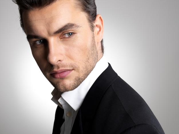 Primer rostro de un joven empresario de moda en poses casuales de traje negro en el estudio