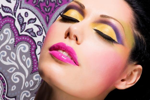 Primer rostro de mujer hermosa con maquillaje de color brillante de moda