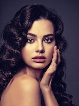 Primer rostro de una mujer hermosa con un maquillaje de ojos ahumado. sexy y hermosa mujer de cabello castaño con cabello largo y rizado. retrato de una atractiva mujer posando.