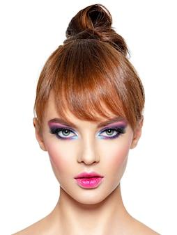 Primer rostro de una mujer hermosa con maquillaje vivo brillante. modelo de moda con maquillaje de ojos creativo - aislado en blanco. chica con cabello pelirrojo. peinado corto con flecos