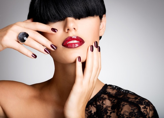 Primer rostro de una mujer con hermosos labios rojos sexy y uñas oscuras