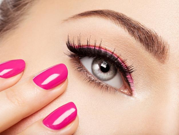 Primer rostro de mujer con uñas rosadas cerca de los ojos. uñas con manicura rosa.