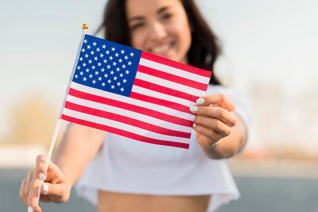 Primer sonriente mujer sosteniendo la bandera de estados unidos