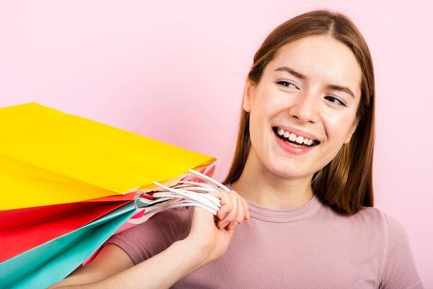 Primer sonriente mujer sosteniendo bolsas