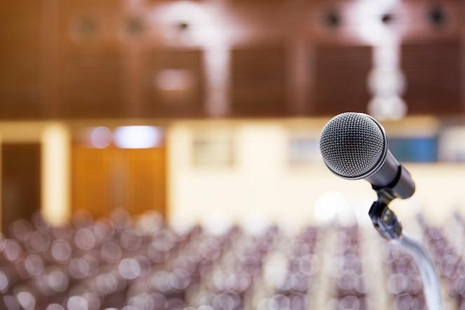 Primer soporte de micrófono con borrosas conferencias de bokeh en el fondo de la sala de reuniones.