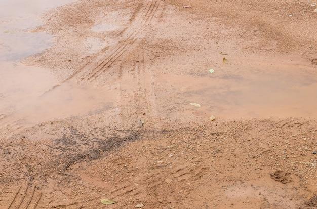 Primer suelo superficial del suelo después de la lluvia con textura de marcas de neumáticos