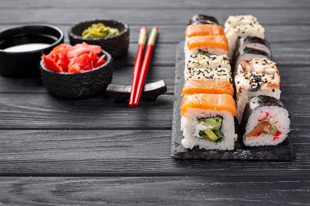Primer surtido de sushi maki en pizarra con palillos
