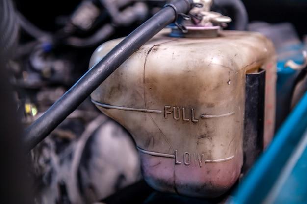 Primer tanque de expansión anticongelante debajo del capó del automóvil. bajo nivel de anticongelante en el automóvil.