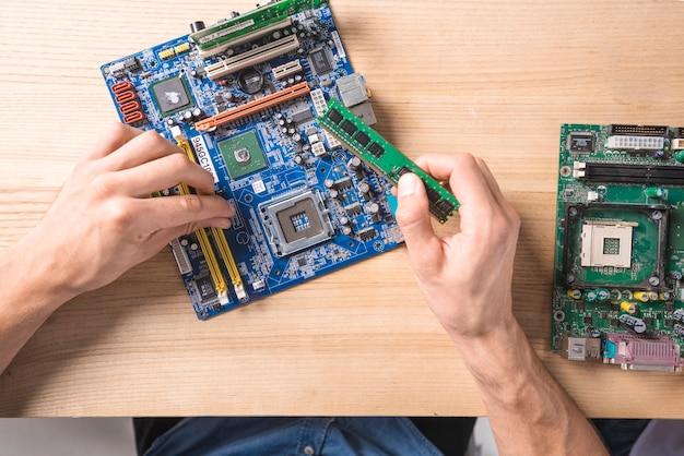 Primer del técnico de sexo masculino de las tic que repara la computadora electrónica del mainboard en la tabla de madera