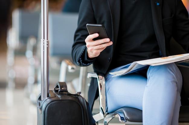 Primer teléfono móvil en manos masculinas en el aeropuerto mientras espera el embarque.