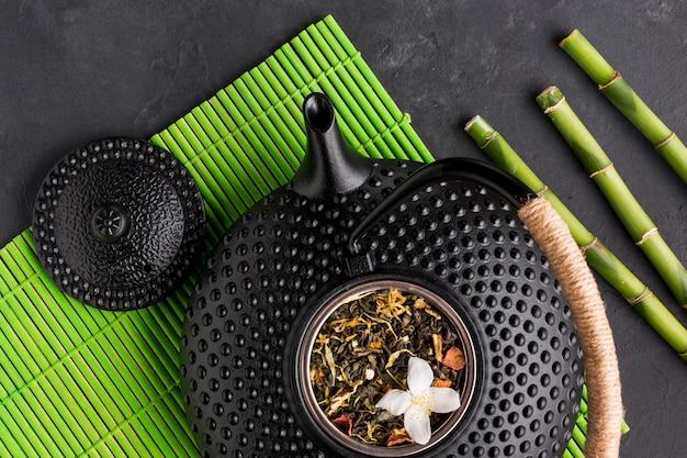 El primer de la tetera de cerámica negra con la hierba seca del té y el bambú se pegan en mantel verde sobre fondo negro