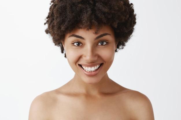 Primer tiro de mujer afroamericana confiada y femenina coqueta con amplia sonrisa brillante posando desnuda satisfecha con gran condición de la piel después del tratamiento cosmetológico