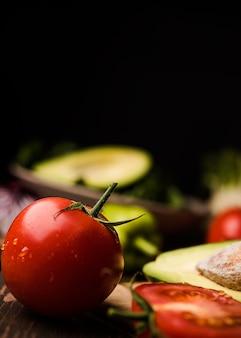 Primer tomate y fondo borroso oscuro