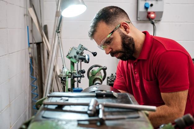 Primer trabajador en gafas uniformes y protectoras trabajando en afilar máquina herramienta