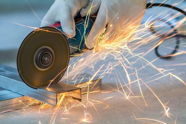 Primer del trabajador que corta el metal con la amoladora. chispas al moler hierro.