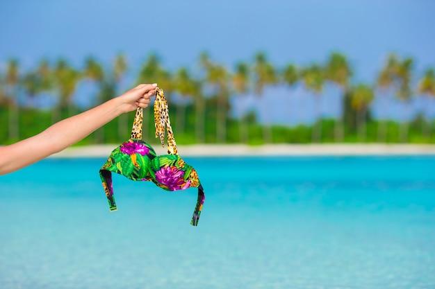 Primer traje de baño sobre fondo de agua turquesa y palmeras