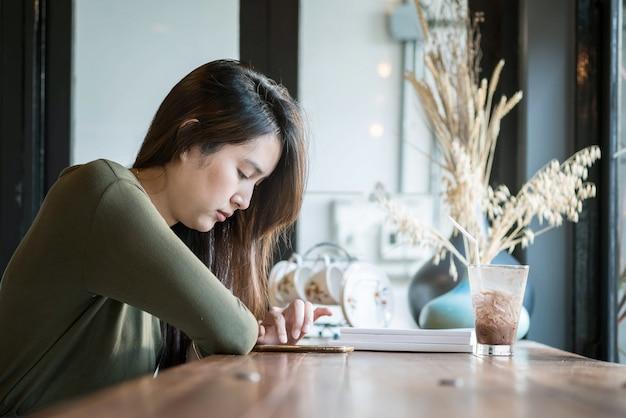 Primer uso de teléfono inteligente de mujer asiática para leer noticias en línea en cafetería