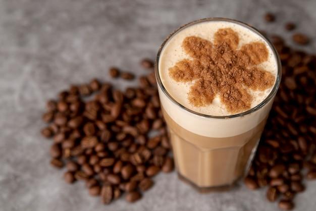 Primer vaso de café con leche con granos tostados
