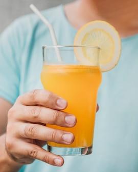 Primer vaso de jugo de naranja natural sostenido a mano