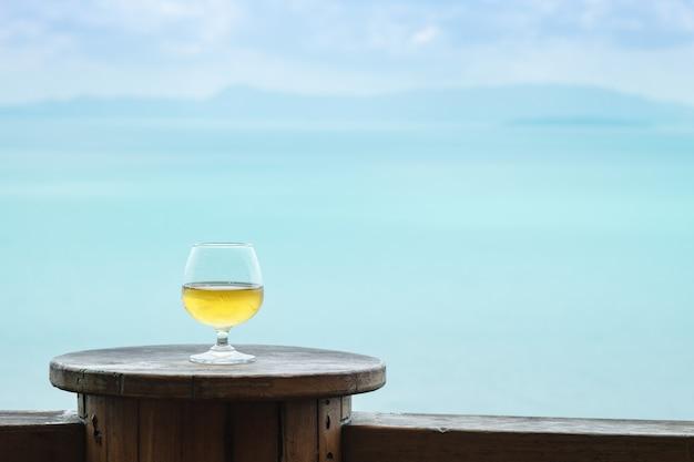 Primer vaso de vino blanco en la mesa en la terraza con vista al mar