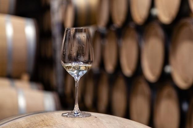 Primer vidrio con vino blanco sobre fondo barriles de madera de roble de vino apilados en filas rectas en orden, antigua bodega de bodega, bóveda.