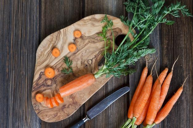 Primer de la zanahoria cruda fresca en el tablero de madera con el cuchillo. vista superior sobre mesa de madera rústica.